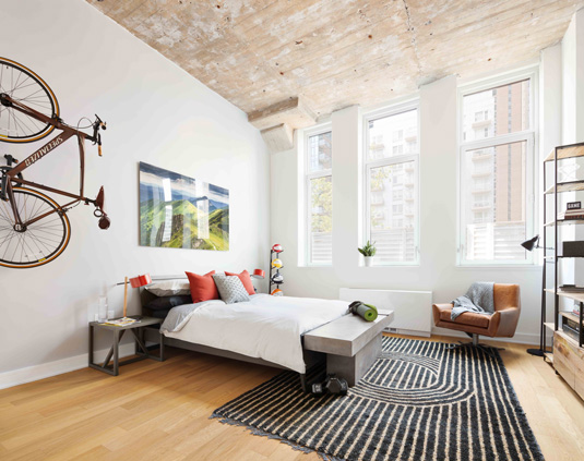 Interior gallery - 3 of 10 - Bedroom with high ceilings and large windows featuring a nice rug at Eagle Lofts