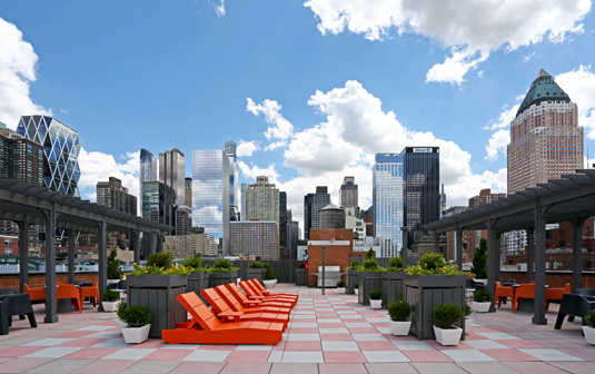 Amenities gallery - 2 of 3 - rooftop at Midwest Court with red lounge chairs